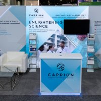Caprion's 10x20 exhibit lives its brand of Enlightening Science with a 8x8 Lightwall. The halo lighting enhances the stand-off graphics and reception counter.