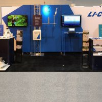 Vision Exhibits designed LI-COR's dream display (easy to set up by booth staff, product displays and accessible storage) using Nomadic Display's FabLite and Envision products. The freestanding sidewall, open display and multi-level counters all have hidden accessible storage. The right hand side of the exhibit can be used in a 10x10 setting.